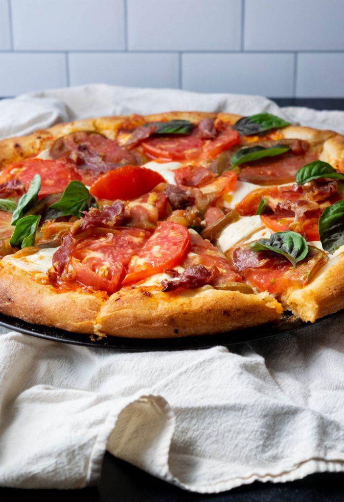 harissa pizza with smoked mozzarella prosciutto and tomatoes