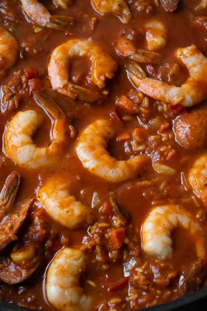 adding the shrimp to the jambalaya